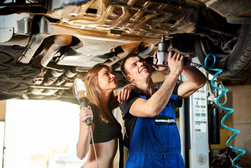 技工加强汽车的底部的螺栓 库存图片