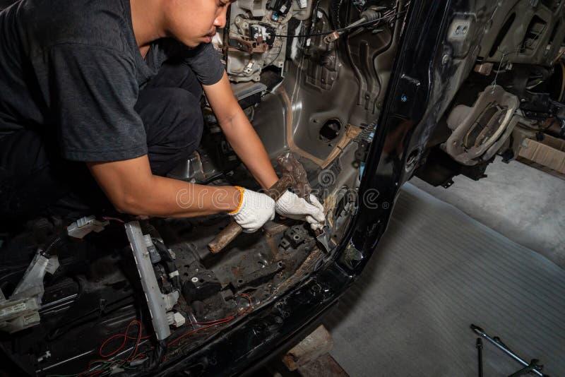 技工在事故以后修理汽车 免版税库存图片