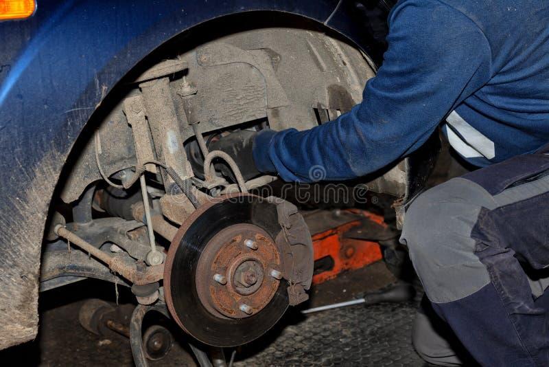技工在他的在修理一辆老汽车的地面上的膝盖工作 库存照片