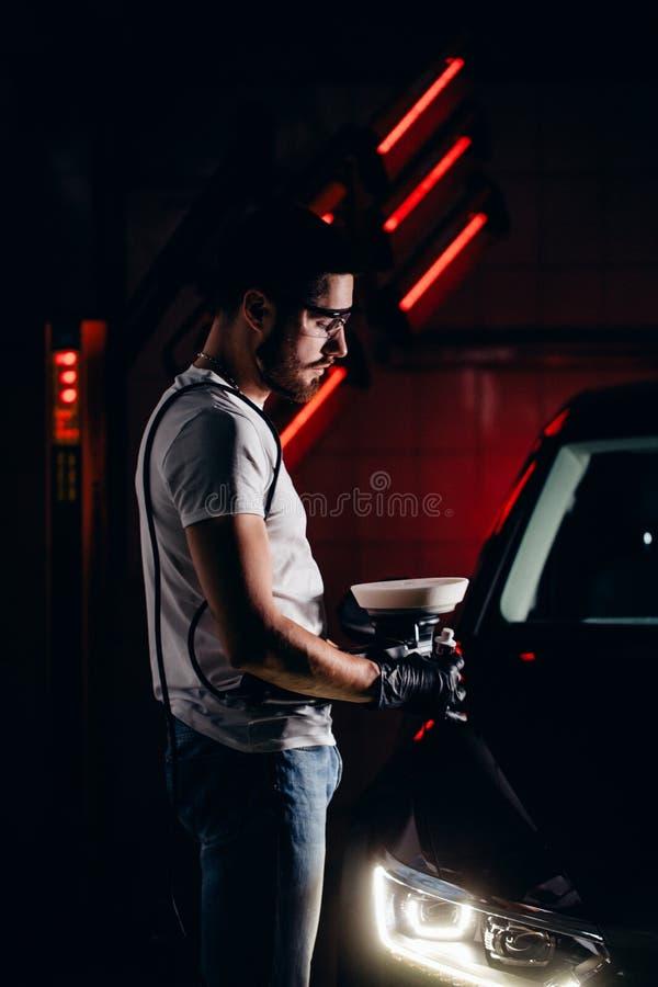 技工工作者为擦亮的汽车做准备由力量缓冲机器 免版税库存照片