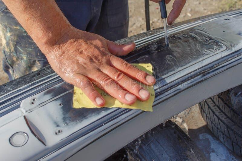 技工工作者安装工铺沙的擦亮的汽车防撞器和准备防撞器绘的在修理期间 库存图片