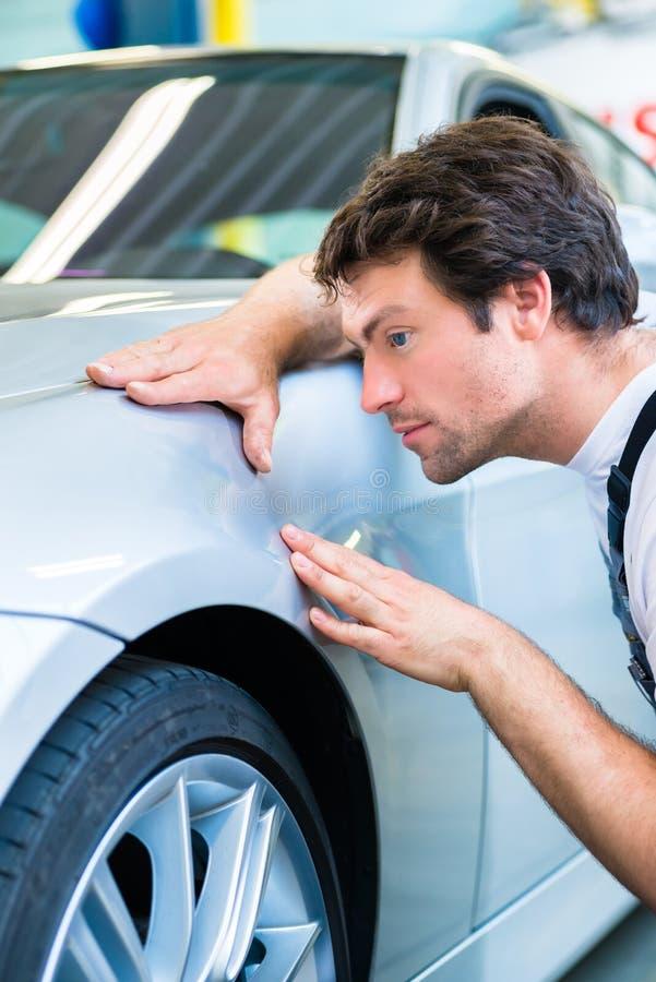 技工控制亮漆在汽车车间 免版税库存图片