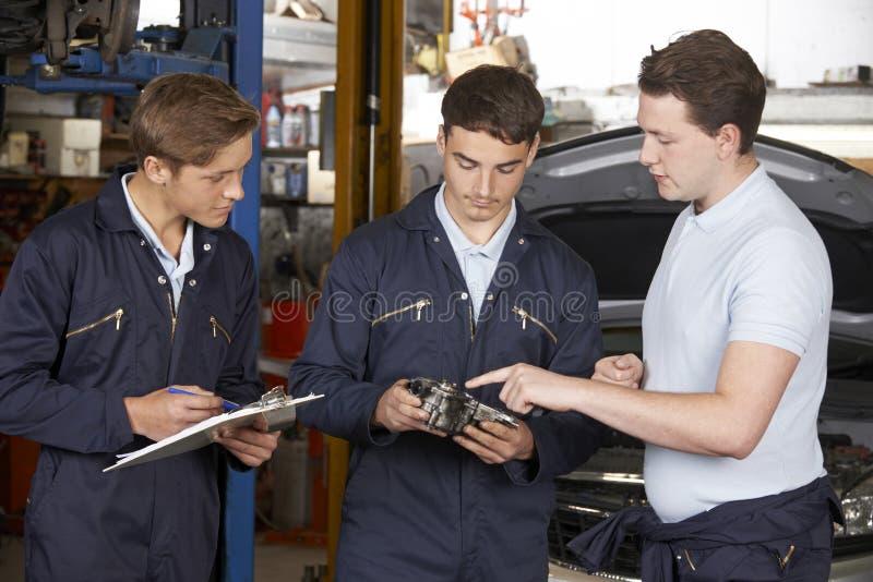 技工教的实习生在车库车间 免版税库存照片