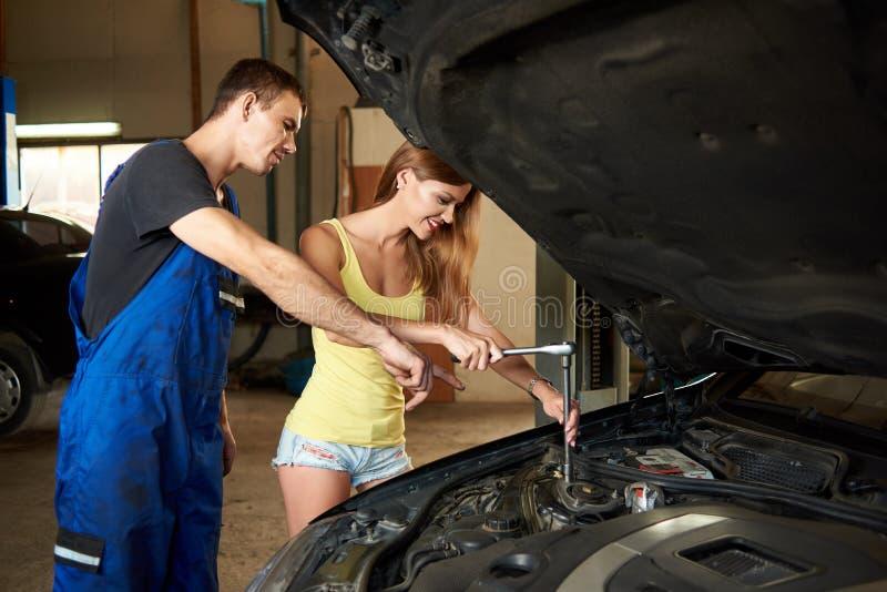 技工显示女孩如何使用板钳修理汽车 免版税库存图片