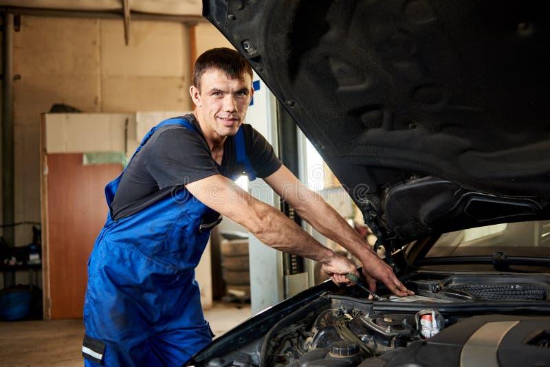 技工特写镜头修理在他的维修车间的汽车 免版税图库摄影