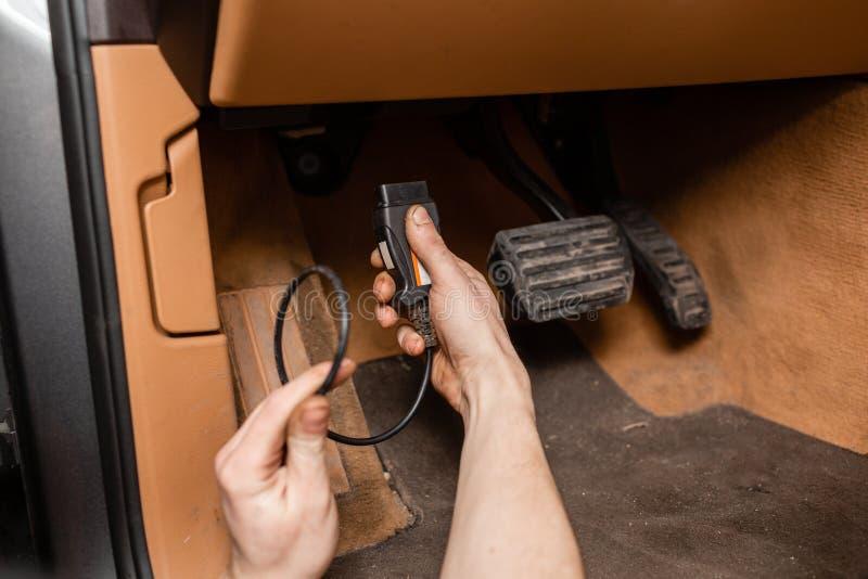 技工连接计算机到机器 汽车修理师在一种诊断片剂帮助下维护一辆车 库存图片