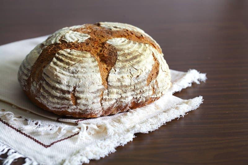 技工黑麦面包大面包,拂去灰尘用面粉,在桌布 免版税库存照片