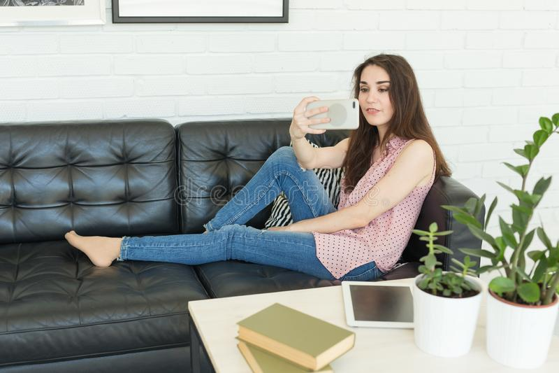 技术、互联网和人概念-做照片使用智能手机和说谎在沙发的年轻深色的博客作者妇女 库存图片