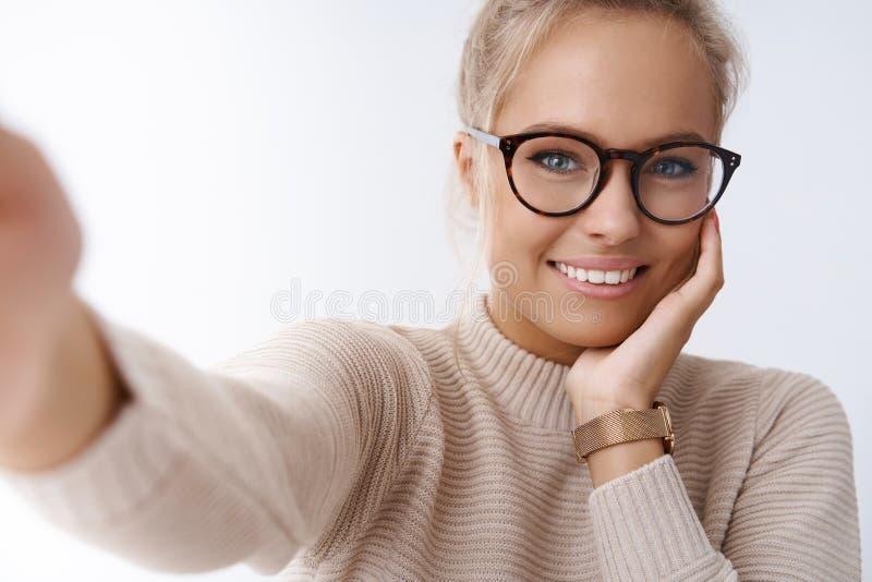 技术、柔软和秀丽概念 采取selfie的嫩悦目女朋友拿着照相机伸出手 免版税库存照片
