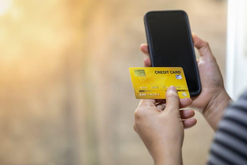 技术、网络购物和电子商务概念 关闭拿着信用卡和巧妙的手机有拷贝的妇女手 免版税库存图片
