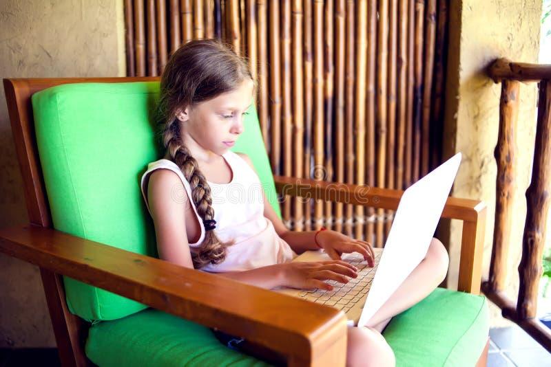 技术、赌博和人概念-使用膝上型计算机comput的女孩 免版税库存照片