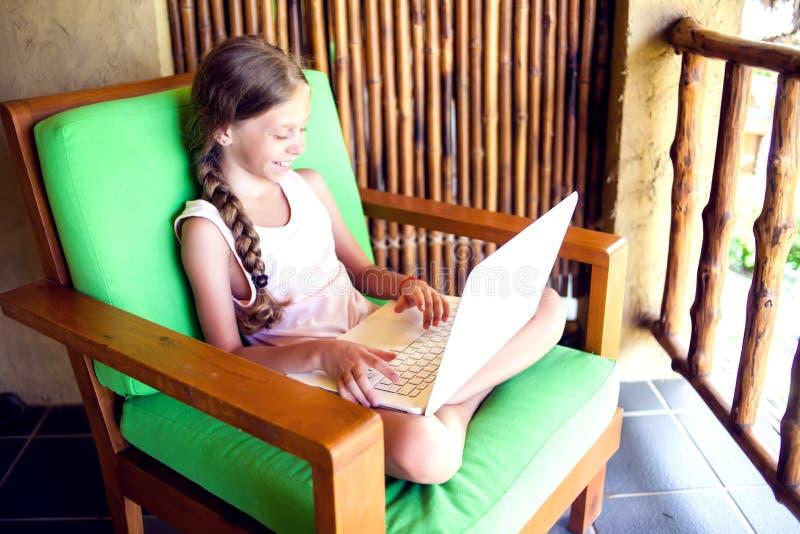 技术、赌博和人概念-使用膝上型计算机comput的女孩 免版税库存图片
