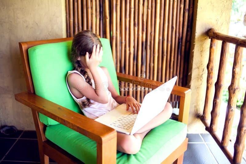 技术、赌博和人概念-使用膝上型计算机comput的女孩 免版税图库摄影