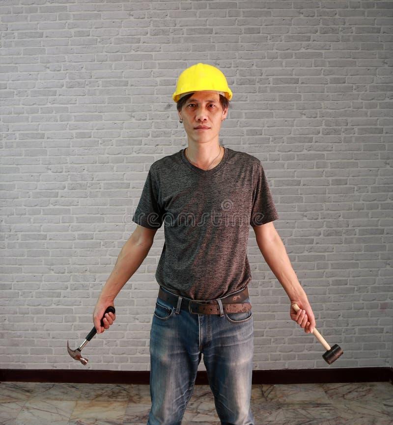 技术员人商品染黄与橡胶深灰T恤杉和牛仔布的牛仔裤在手中站立和和钢锤子的盔甲 免版税库存图片