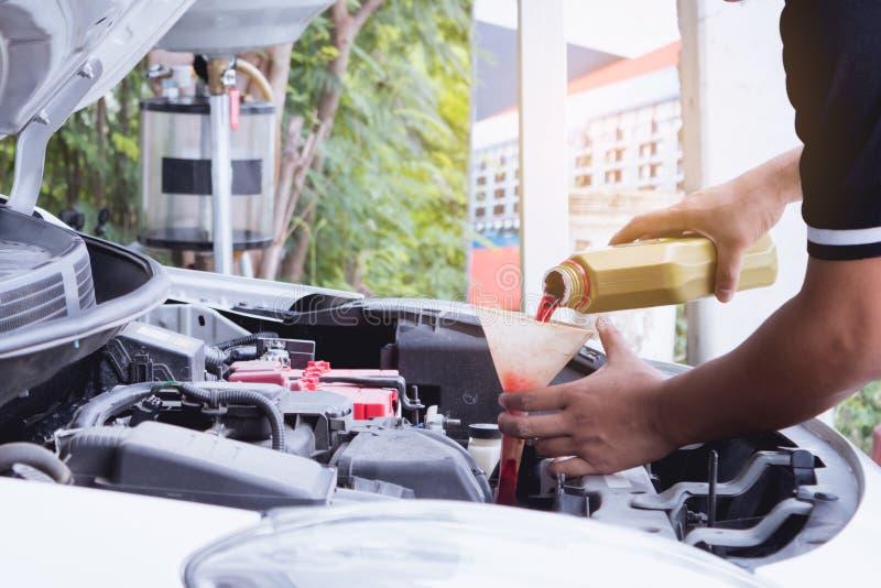 技术员人对引擎的积土油 图库摄影