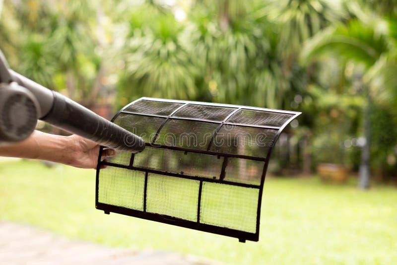 技术员人烘干并且拂去清洁空调器过滤器w的灰尘 免版税图库摄影
