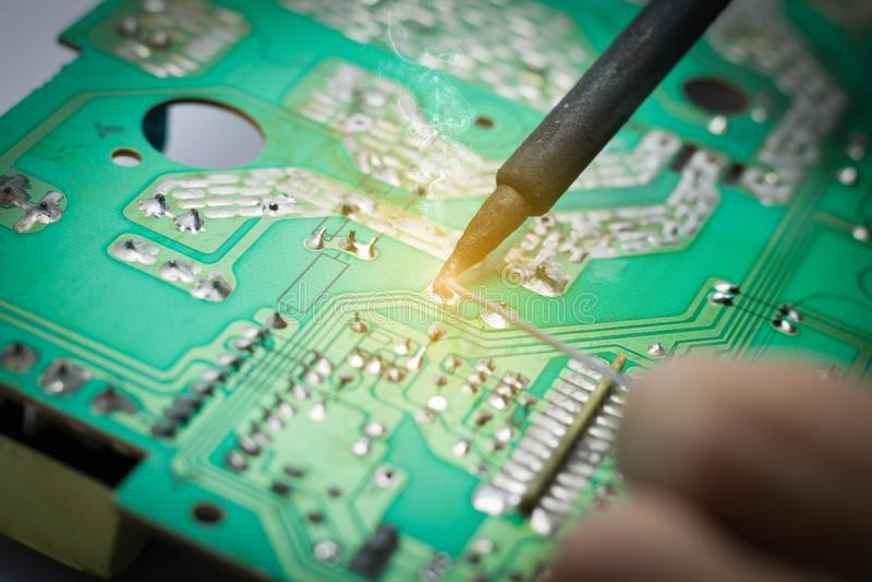 技术员修理电子线路 罐子焊接的零件 免版税库存照片