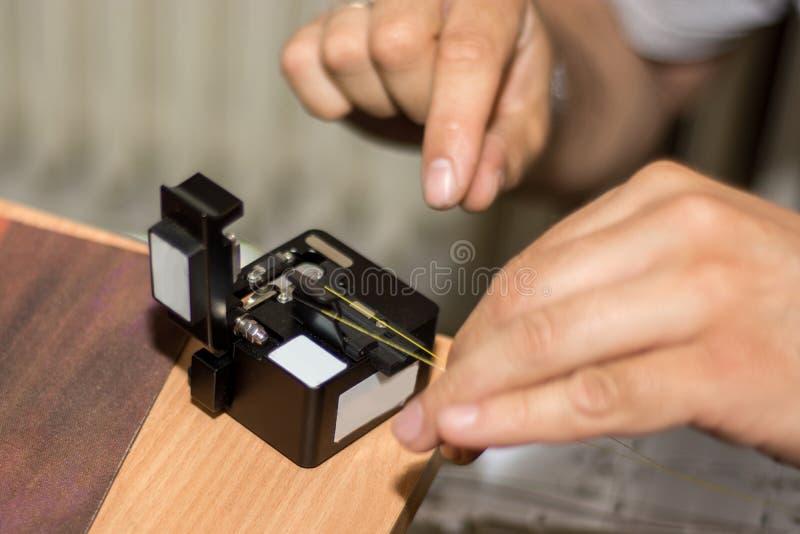 技术员切开与切割工具的光纤并且为接合做准备 免版税库存照片