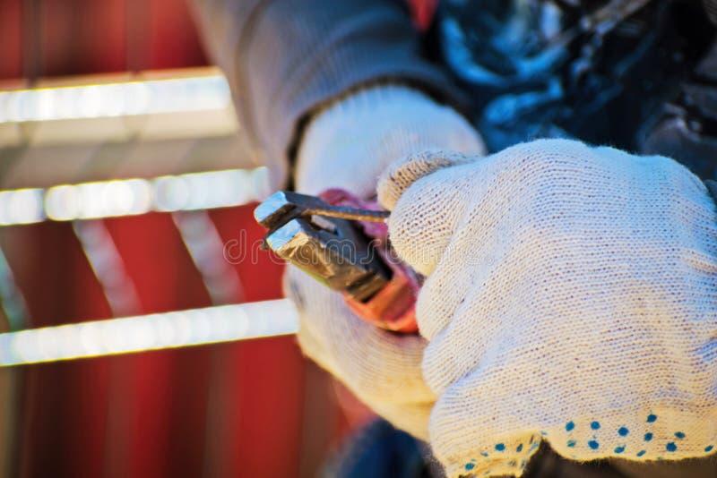 技术员在他的有钳子的手保留弯曲金属棒 钳子在人的手上 电工 免版税库存照片