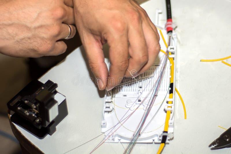 技术员在光纤接合盘子投入了它光导电缆和导线 免版税库存图片