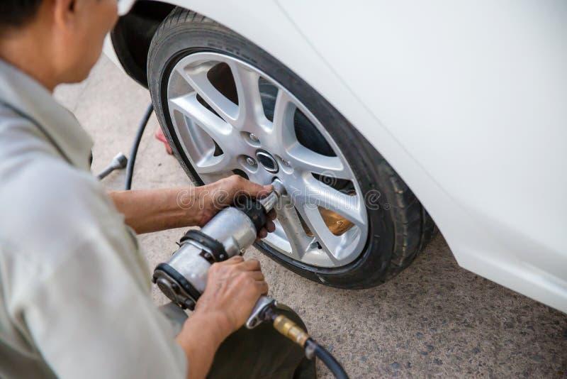 技术员工作者拧紧有一把手工板钳的轮子螺栓 维护和检查汽车概念 的检查和定象veh 库存照片