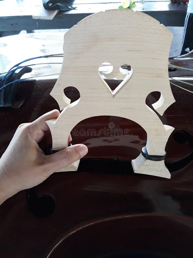 技术员拿着木头调整声音 低音提琴仪器 库存图片
