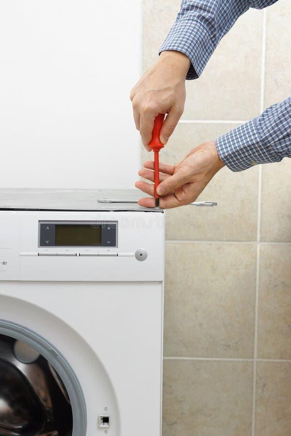 技术员有螺丝刀的定象洗衣机 免版税库存照片