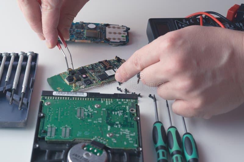 技术员的手供以人员设法替换在残破的手机的组分 免版税图库摄影