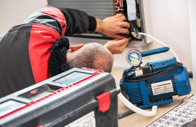 技术员真空泵撤出和检查新的空调器 库存照片