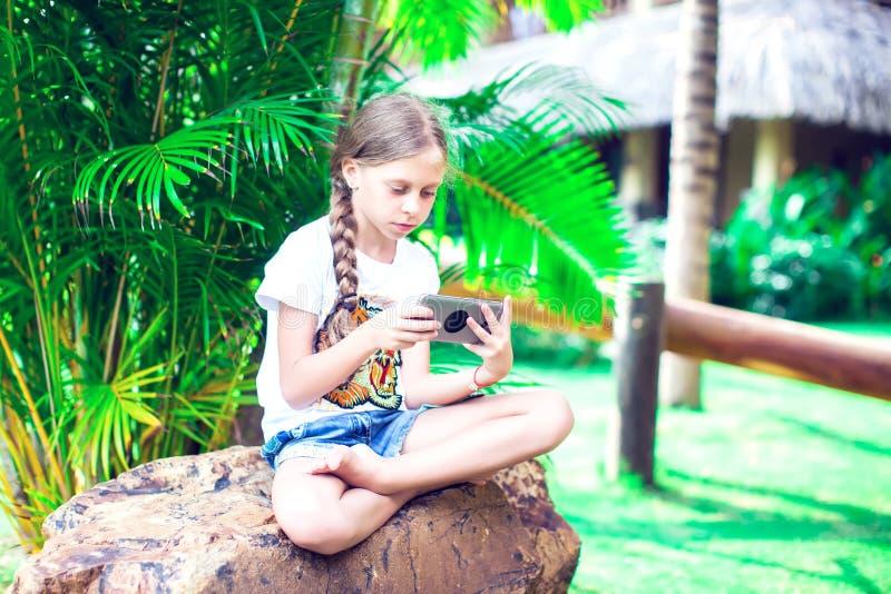 技术和人概念-使用smartph的愉快的微笑的女孩 免版税图库摄影
