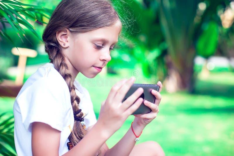 技术和人概念-使用smartph的愉快的微笑的女孩 库存图片
