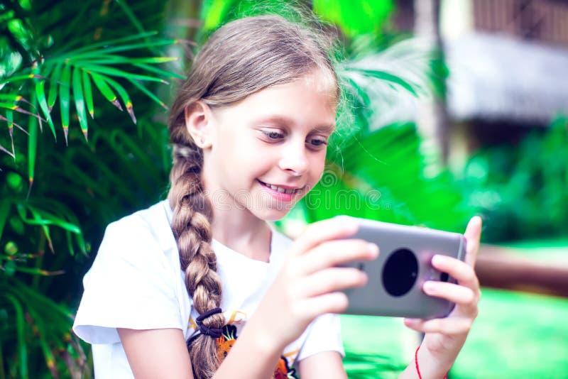 技术和人概念-使用smartph的愉快的微笑的女孩 图库摄影