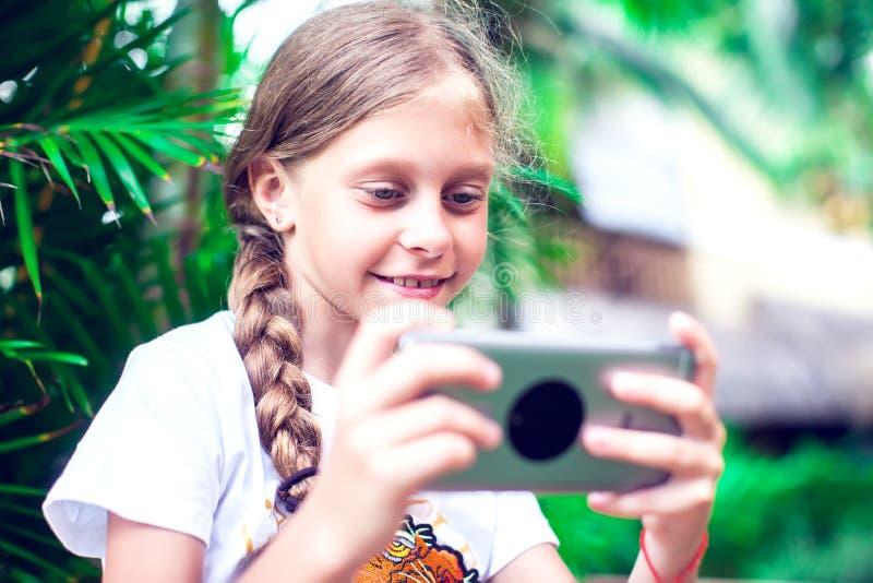 技术和人概念-使用smartph的愉快的微笑的女孩 免版税库存照片