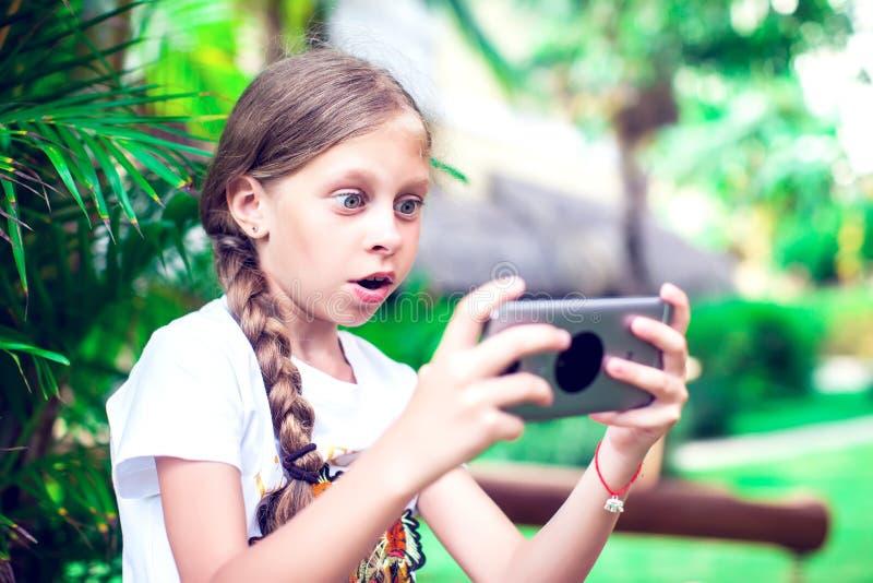 技术和人概念-使用smartph的愉快的微笑的女孩 免版税库存图片