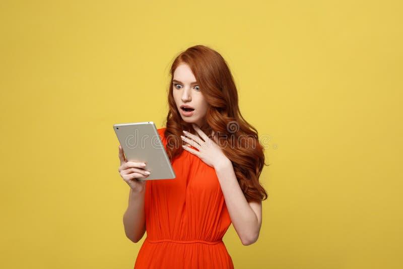 技术和生活方式概念:穿橙色礼服的惊奇的少妇穿衣使用在生动隔绝的片剂个人计算机 免版税库存图片