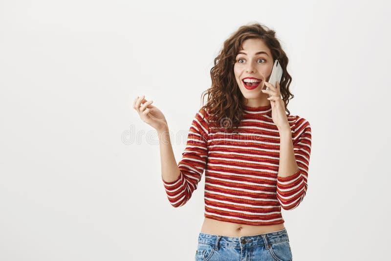 技术团结世界 兴奋的和激动的白种人女孩画象有卷发和红色唇膏的,打手势 免版税库存图片