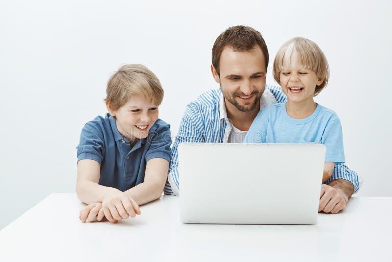 技术团结家庭 广泛地微笑愉快的美丽的父亲和的儿子画象坐在膝上型计算机附近和,有 免版税库存图片