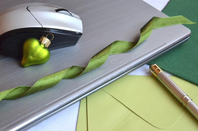 技术在圣诞节期间的工作 有老鼠、笔、短信卡和绿色圣诞节球装饰的闭合的便携式计算机 图库摄影