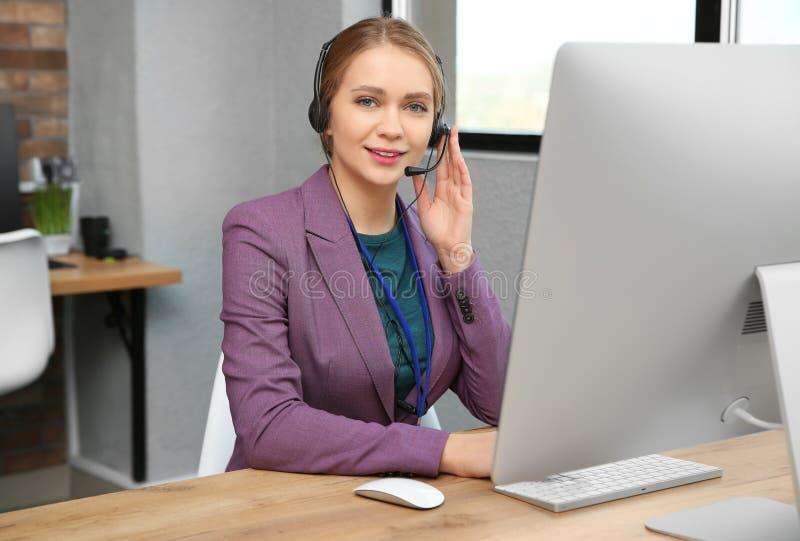 技术支持操作员与耳机和计算机一起使用在桌上 库存照片