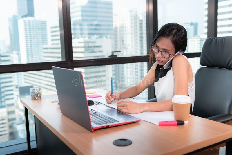 技术智能手机和通信概念,女商人画象在办公室工作场所拜访手机 ?? 免版税库存照片