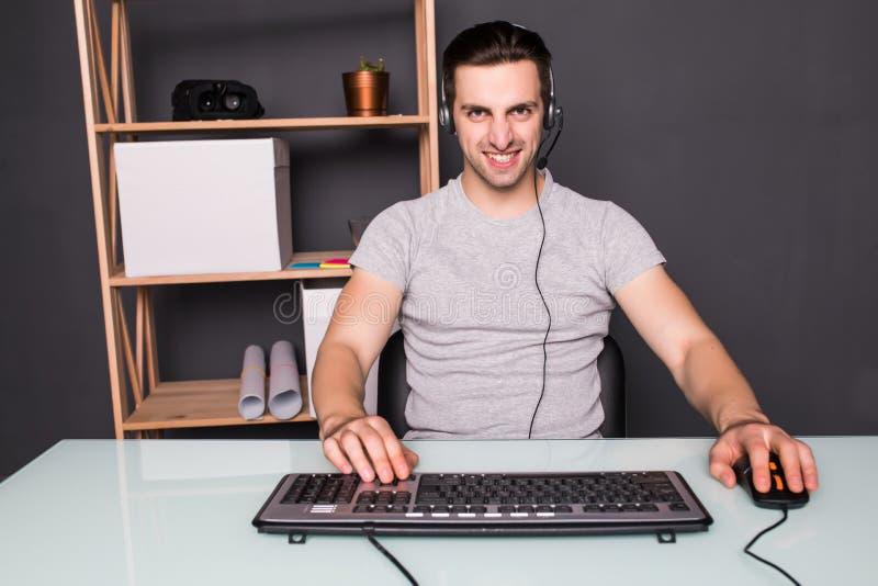 技术,赌博,娱乐,让` s戏剧和人概念-耳机的恼怒的叫喊的年轻人有个人计算机计算机使用的 免版税库存照片