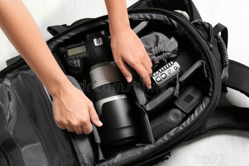 把专业摄影师的设备放的妇女入背包在地板上 免版税图库摄影