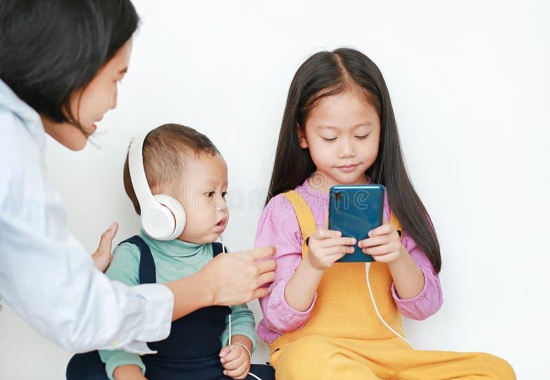 把亚裔姐姐和弟弟带的母亲分享对由被隔绝的智能手机享受与耳机的听的音乐  库存照片