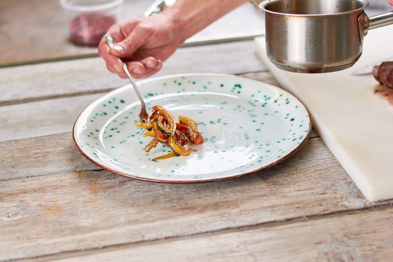 把从平底深锅的厨师菜放在板材上 免版税库存照片