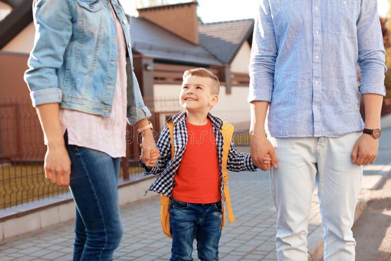 把他们的小孩带的年轻父母对学校 免版税库存图片