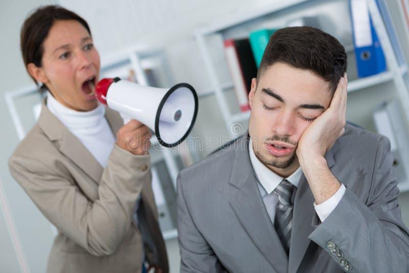 把他吵醒的商人睡觉在工作场所的和女实业家 图库摄影