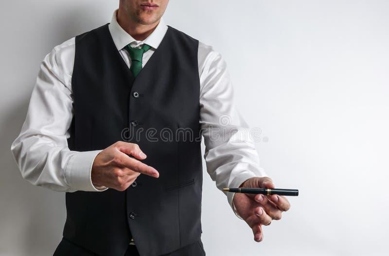 把他的手指指向的商人顾客的一支笔能签合同 免版税图库摄影