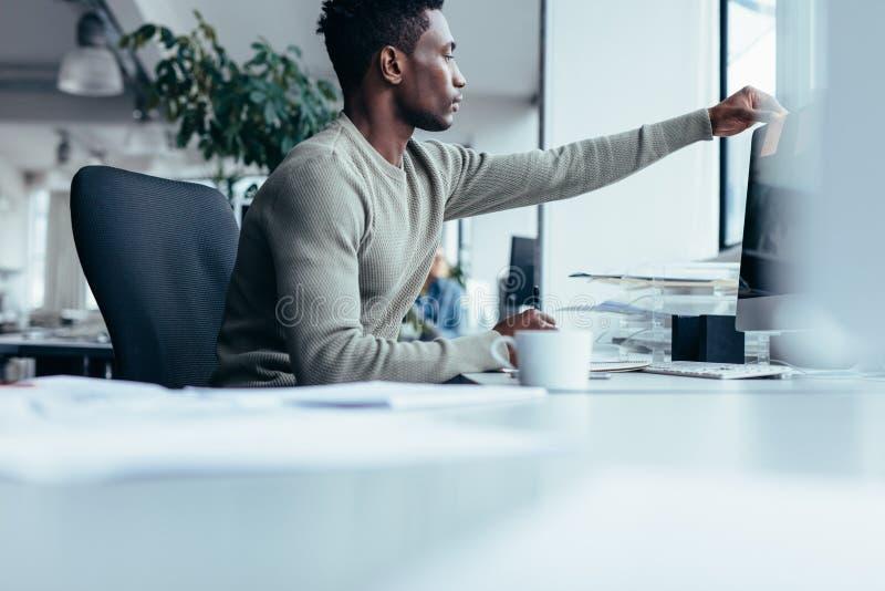 把便条纸放的非洲人在计算机显示器上 免版税库存照片