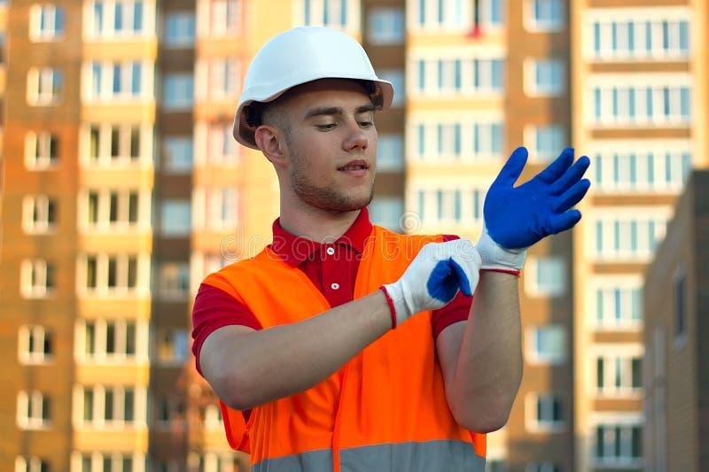 把保护手套放在手上和换衣服为工作的建造者 免版税库存照片