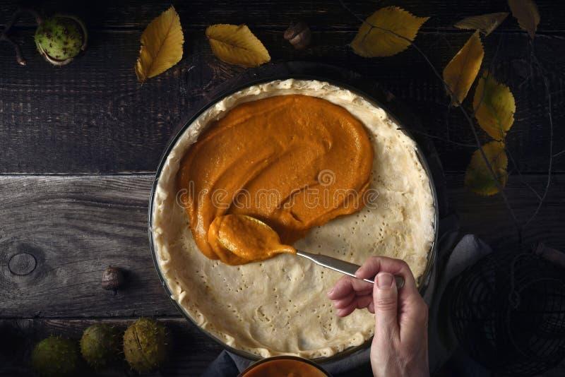 把南瓜纯汁浓汤放在南瓜饼的面团上在木桌上 库存照片